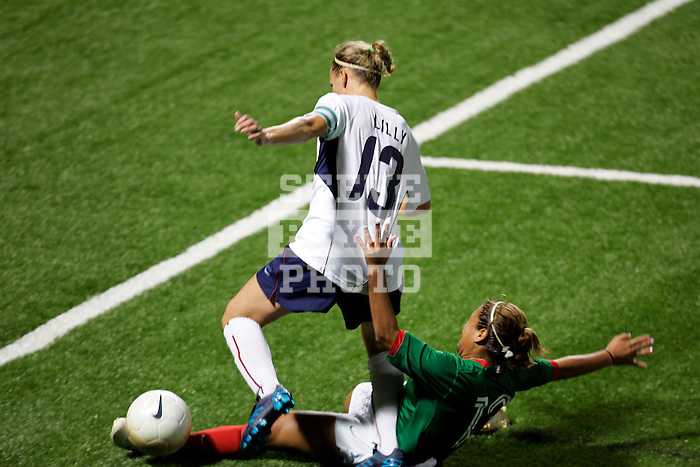 Mexico defender Isabel Valdez (13) slides to take the ball from USA forward Kristine Lilly (13).  The U. S. Women's National Team defeated the National Team of Mexico 3-1 in an international friendly at PAETEC Park, Rochester, New York, on September 13, 2006.