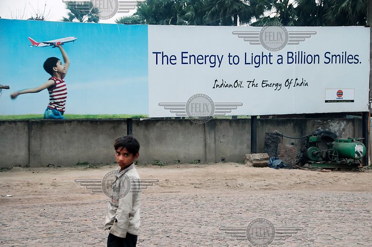 A boy stands in front of a large advertisement for Indian Oil at a petrol station.
