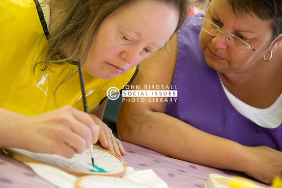Day Service Care Assistant supervising service users with learning disabilities in painting session,