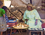 "A woman sells ""masas"" (flour pancakes served with spices) to travelers in Fada N'Gourma on the road connecting Burkina Faso with neighboring Niger."