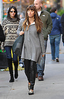Jessica Biel strolling in New York City in leather trousers and grey cape coat.