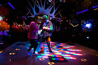 """Couple dancing in an empty bar.Northern Mexico is very polarized in sense of social status. In the red zone of Ensenada - """"El Bajio"""", people of considered """"low-class"""" have their share of night life. Alcoholics, prostitutes, drug junkies and the simple survivors find cheap beer and  entertainment.."""