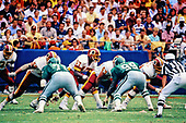 Washington Redskins quarterback Doug Williams (17) calls signals during the game against the Philadelphia Eagles at RFK Stadium in Washington, DC  on September 13, 1987.  Pictured, from left to right: Redskins running back Keith Griffin (35); Redskins right offensive tackle Russ Grimm (68); Eagles left defensive tackle Ken Clarke; Williams; Redskins center Jeff Bostic (53);  Eagles right defensive tackle Jerome Brown (99); and  Redskins left guard Raleigh McKenzie.  The Redskins won the game 34 - 24.<br /> Credit: Ron Sachs / CNP