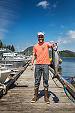 USA, Alaska, Ketchikan, a fisherman holds up a catch made in Behm Canal near Clarence Straight, Knudsen Cove along the Tongass Narrows
