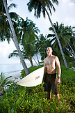 INDONESIA, Mentawai Islands, Kandui Surf Resort, portrait of mature man standing with surfboard