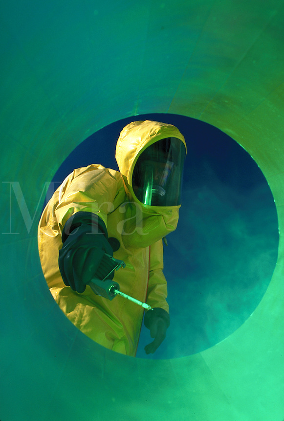 Hazardous materials worker, firefighter, reaching into a cylinder holding testing equipment