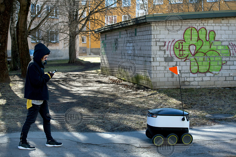 Kadri Salu, testing a delivery bot on the street for robotic delivery company Starship.