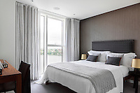 A bedroom with a grey patterned wallcovering and a double bed with an upholstered headboard in a check pattern fabric. The room has a floor to ceiling window with full length curtains in a stripe pattern.