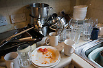 Piled up mess of dirty plates and pots in a domestic kitchen, UK