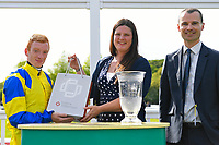 Jockey Edward Greatrex receives his prize from sponsors after winning The Smith & Williamson Handicap (Class 6)     during Afternoon Racing at Salisbury Racecourse on 17th May 2018
