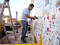 NWA Democrat-Gazette/BEN GOFF @NWABENGOFF<br /> Jose Hernandez with AMP Sign &amp; Banner in Bentonville uses a heat gun and foam roller on Monday Nov. 9, 2015 to install the final product of the Walmart Museum's Community Art Project 2015 on the side of the new Bentonville Square Walmart Neighborhood Market. The Walmart Museum launched the project during October's First Friday, with the public encouraged to submit drawings based on the theme of 'community' or 'innovation,' which where scanned and printed on the vinyl wraps.