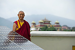 A monk poses for a photograph with some solar panels at Kopang Monastery. 