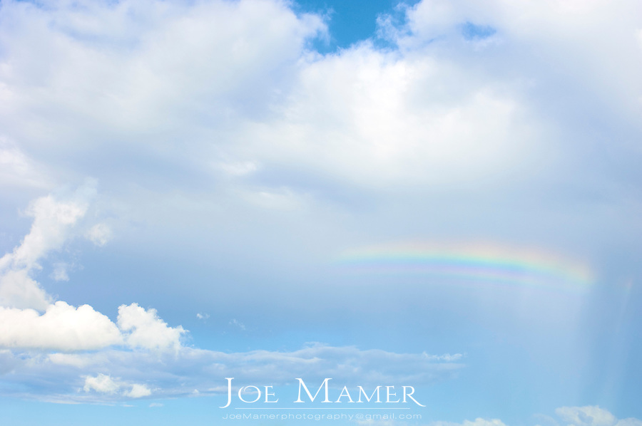 Rainbow in blue sky with few clouds.