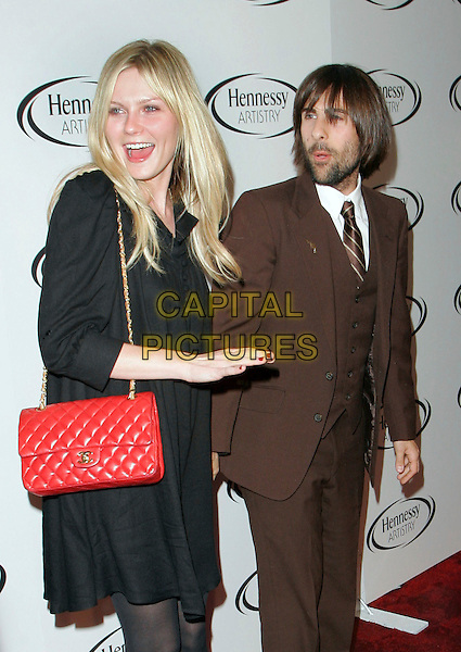 "KIRSTEN DUNST & JASON SCHWARTZMAN.At Hennessy event to present the ""Global Art of Mixing"" at Capitiale, New York, New York, USA..October 17th, 2006.Ref: ADM/JL.half length black dress red brwon suit mouth open purse no make-up make up.www.capitalpictures.com.sales@capitalpictures.com.©Jackson Lee/AdMedia/Capital Pictures."
