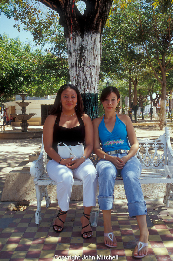 Two young Mexican women sitting on a bench in the main square of The 18th-century Spanish colonial mining town of Concordia near Mazatlan, Sinaloa, Mexico