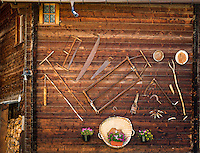 Switzerland, Canton Valais, Evolène: village at valley Val d'Hérens - agricultural equipment decorating the facade of a wooden house | Schweiz, Kanton Wallis, Evolène: Dorf im Val d'Hérens (Eringertal) - landwirtschaftliche Geraete als Dekoration an einer Hausfassade