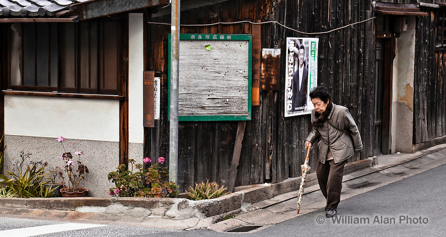 An elderly woman hobbles about a narrow street in Nara Japan January 2010