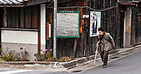 An elderly woman hobbles about a narrow street in Nara Japan January 2010