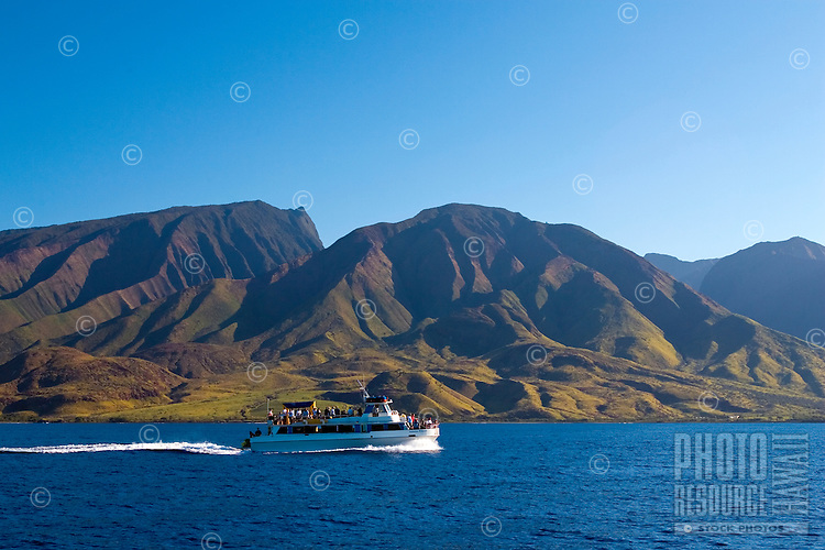 The Lahaina Princess boat cruises in front of the West Maui Mountains on a crystal clear day.