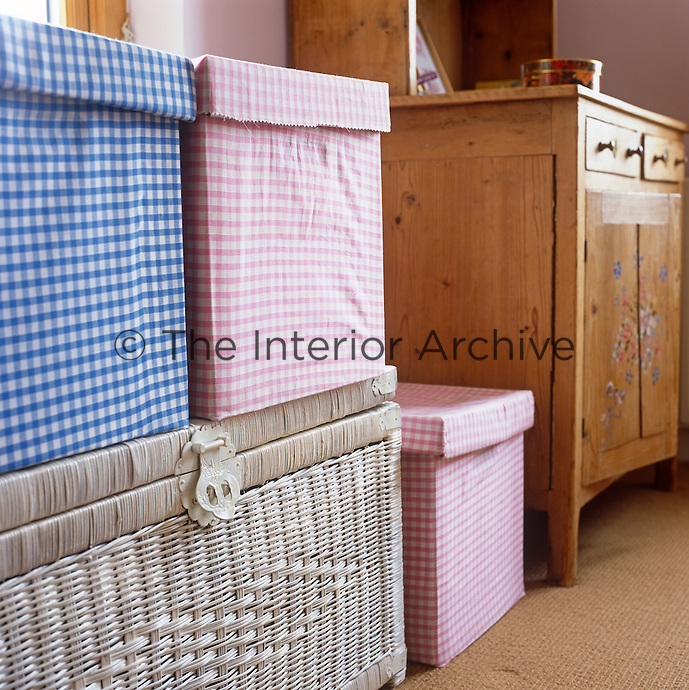 Checked patterned boxes on top of a wicker trunk are used to store toys in a child's bedroom