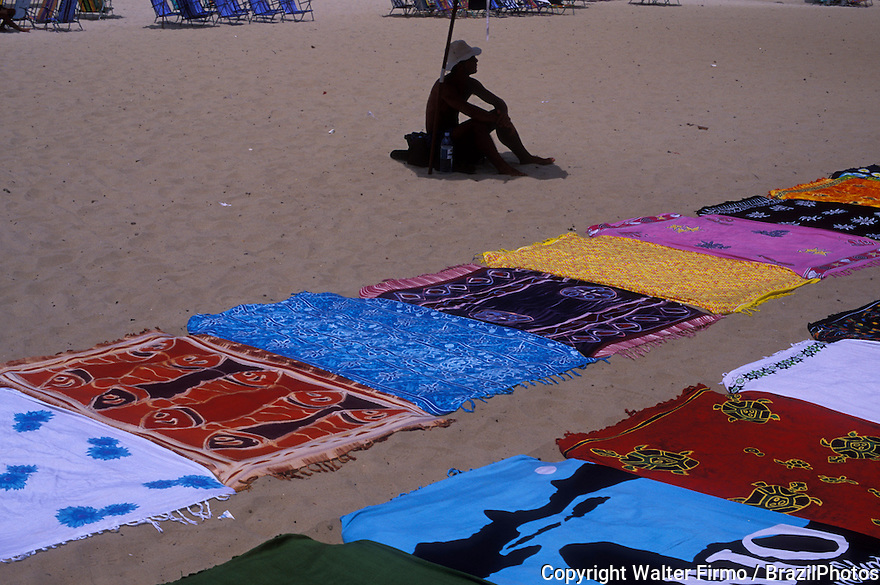 Street vendor at Copacabana beach, Rio de Janeiro, Brazil. Towels for sale, street-seller, informal economy, open-air market.