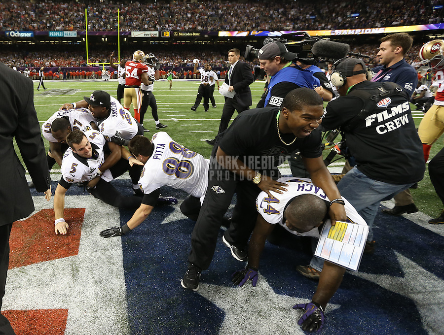 Feb 3, 2013; New Orleans, LA, USA; Baltimore Ravens quarterback Joe Flacco (5) is tackled by his teammates in celebration after defeating the San Francisco 49ers in Super Bowl XLVII at the Mercedes-Benz Superdome. Mandatory Credit: Mark J. Rebilas-