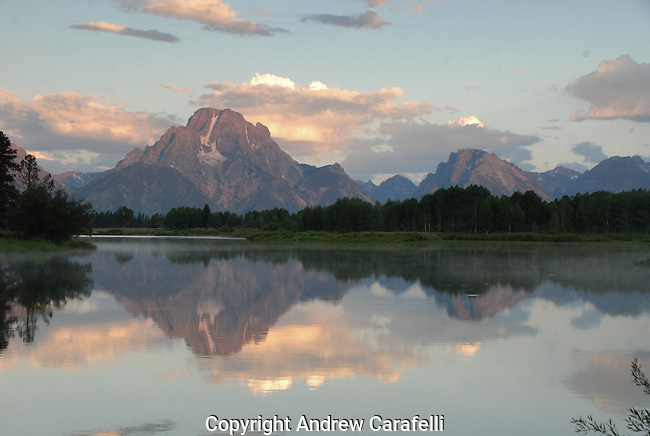 The still waters of Oxbow Bend in the Tetons provide a perfect reflection of 13,605 foot Mt Moran at sunrise.
