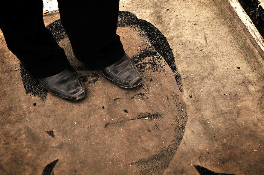 Homme marchant sur un paillasson à l'éfigie de Ben Ali, Redeyef