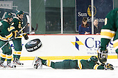 "Drew MacKenzie (Vermont - 2) ""slides into home"" as part of his goal celebration as Colin Markinson (Vermont - 6) and Kyle Reynolds (Vermont - 9) look on. - The University of Massachusetts (Amherst) Minutemen defeated the University of Vermont Catamounts 3-2 in overtime on Saturday, January 7, 2012, at Fenway Park in Boston, Massachusetts."