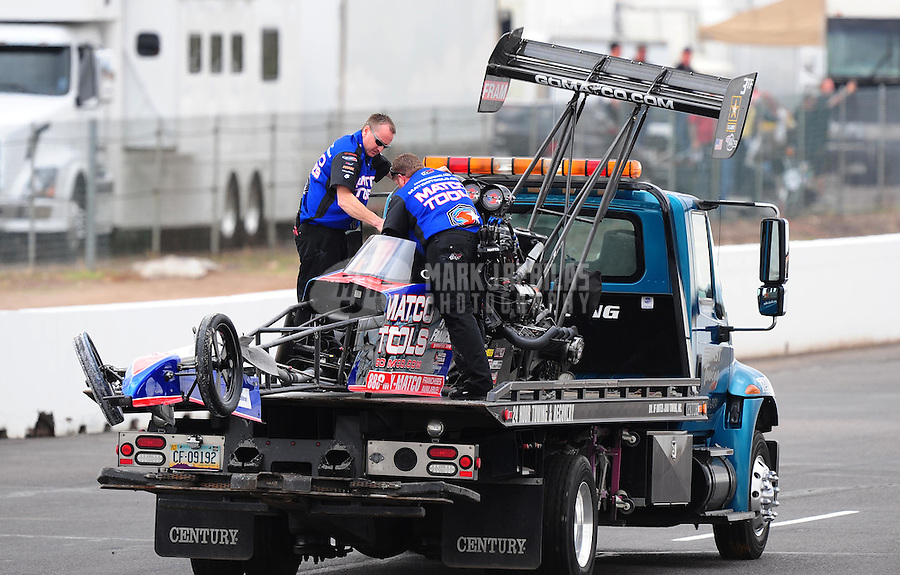 Feb. 21, 2010; Chandler, AZ, USA; The car of NHRA top fuel dragster driver Antron Brown is towed back to the pits after crashing during the Arizona Nationals at Firebird International Raceway. A tire from his car flew over the trackside wall and into a spectator area killing a female fan. Mandatory Credit: Mark J. Rebilas-