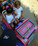 Emma Valle,4, of Babylon gives Justin Alvarez,4 of Deer Park, instructions on seatbelt use in her toy Jeep before taking him for a ride at Argyle Lake Park in Babylon on Monday August 13, 2007. Photograph by Jim Peppler. Copyright / Jim Peppler