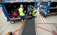 From left, American Airlines Fleet Service Clerks James Webster Jr. (cq) and Dave Purdie (cq) load baggage on a plane at Dallas-Fort Worth International Airport (DFW) in Dallas, Texas, Friday, May 14, 2010. ..PHOTO: MATT NAGER