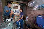 "Larren Jo ""LJ"" Bacilio, a teacher in the Alternative Learning System of the Kapatiran-Kaunlaran Foundation (KKFI), talks with one of his students at his home in the Tondo neighborhood of Manila, Philippines. <br /> <br /> KKFI is supported by United Methodist Women."