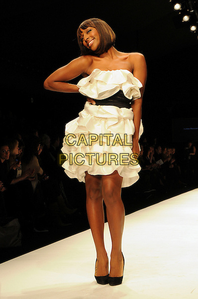 ALEXANDRA BURKE .The Fashion For Relief Haiti 2010 show for London Fashion Week Autumn/Winter 2010 at Somerset House, London, England..February 18th, 2010.LFW catwalk runway full length black layered layered dress strapless sash hand on hip.CAP/CAS.©Bob Cass/Capital Pictures.