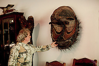 "Los Angeles, California, November 14, 2009 - Ernie Wolfe straitens an African mask hanging on the wall of his living roomhome The Wolfe's own the Ernie Wolfe Gallery and are the most reknowned African at dealers in the country. He has says, ""I have been a collector since I was a kid, but it was my first trip to Africa in the 70's that got me hooked.""..CREDIT: Daryl Peveto/LUCEO for The Wall Street Journal.Homefront - Ernie Wolfe #1348."