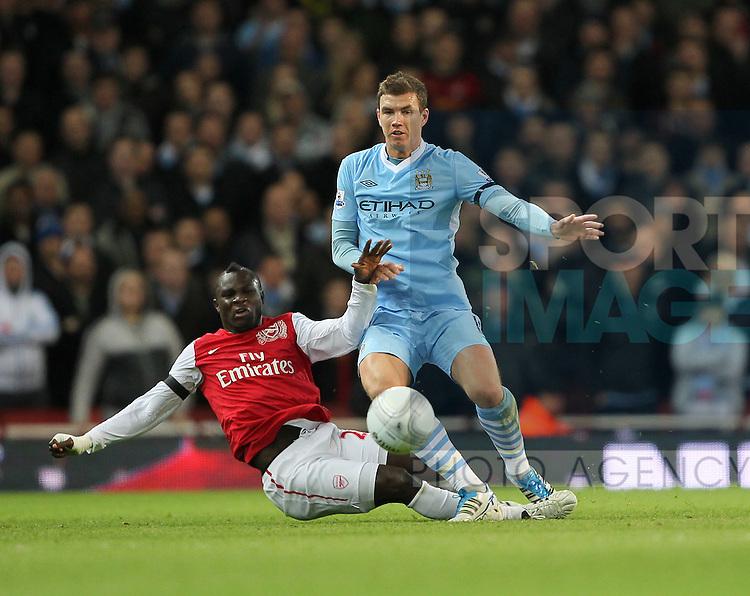Arsenals Emmanuel Frimpong tussles with Manchester Citys Edin Dzeko