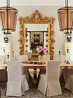 An 18th-century Italian gilt mirror takes center stage in a luxurious dining room; the table is made of oak and bronze, and the chairs are slip- covered in Egyptian linen.