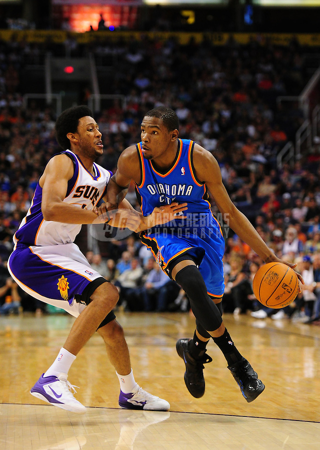 Mar. 30, 2011; Phoenix, AZ, USA; Oklahoma City Thunder forward Kevin Durant controls the ball against Phoenix Suns guard Josh Childress in the second half at the US Airways Center. The Thunder defeated the Suns 116-98. Mandatory Credit: Mark J. Rebilas-