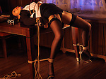 Sexy asian lady lying tied up with Japanese rope bondage Shibari on a table in a provocative pose