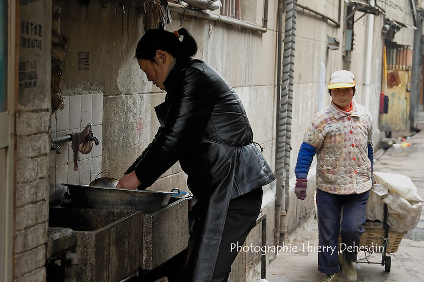 A lady living  in a Lilong, washing her cooking tools in the alley. .Shanghai, February 2006.