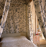 Detail of the patterned blue and white fabric of the bed canopy and curtains