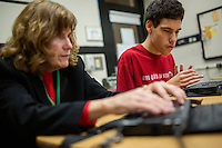 Jamie LeDuc, 15, (in red) uses a BrailleNote Apex Notetaker in computer class with Kate Crohan, Teacher of the Visually Impaired in the Secondary Program at Perkins School for the Blind in Watertown, Massachusetts, USA, on Tues., Oct. 15, 2013. The Apex has wifi capabilities and works as a word processor, web browser, calculator, and email device. LeDuc has been at Perkins since the beginning of the 2012-2013 school year. LeDuc is learning how to use the Apex Notetaker. Here, Crohan is teaching him about how email management works on the device and what to do about spam email. LeDuc was happy to get his email inbox down to zero messages during this session. Emails and other documents are displayed in braille across the bottom row of the device.