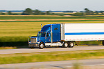 Rolling down I-57 in east central Illinois, a blue semi tractor trailer rig is up to speed and shown in a panning shot capturing it's fast motion.