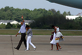 Cape Cod, MA - August 23, 2009 -- United States President Barack Obama, accompanied by his oldest daughter Malia, 11, followed by his wife Michelle and daughter Sasha, 8, leave Air Force One after the First Family landed at Cape Cod Coast Guard Air Station on Cape Cod, Massachusetts Sunday, August 23, 2009. The First Family then boarded a US Marine helicopeter for their week-long vacation on Martha's Vineyard, Massachusetts. .Credit: Vincent DeWitt - Pool via CNP