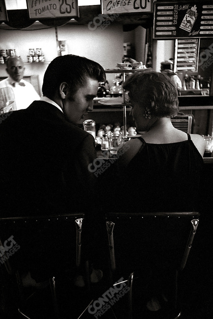 Elvis having a coffee with a girl he just met. A bit later, she is going to become the girl of the kiss. Richmond, Virginia, USA, June 30, 1956