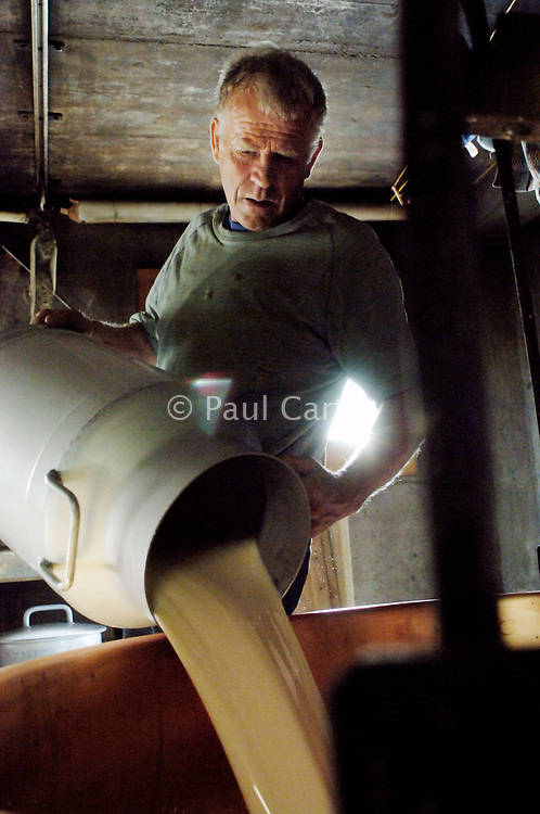 Pouring the morning's milk from the churns into the cauldron...Cowherd and cheesemaker spends 100 days in the summer, high up in the mountains, tending cows and pigs and making cheese at Balisalp and Käserstatt near Meiringen, Switzerland.