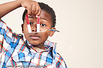 6 year old boy using horse shoe magnet to pick up metal object spoon vertical
