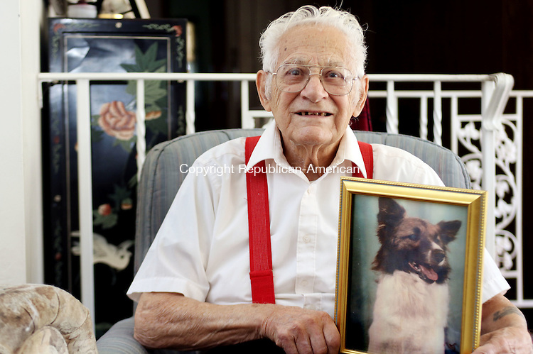 WATERBURY CT. 08 November 2016-110816SV02-Frank Barbino sits with a portrait of his dog from years ago at his home in Waterbury Thursday. Barbino served at Pearl Harbor at the end of WWII (non combat). There, he adopted a dog that he shipped home. Together, they rode all over Waterbury on a motorcycle. Recently, they were reunited when a portrait of the dog was found at a relative's house. <br /> Steven Valenti Republican-American