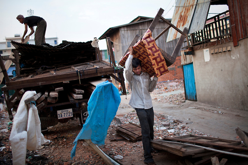 Men remove building materials and furniture from homes demolished in Village 24 of Srah Chak commune, in Phnom Penh's Daun Penh district, March 4, 2011.