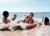 May 22nd 2004-Com, East Timor-A Timorese collage kid on holiday plays with friends in the sand on a beach near the town of Com. Com is located in Lautem district and is known for it's beautiful beaches and great diving.  Photograph by Daniel J. Groshong/Tayo Photo Group